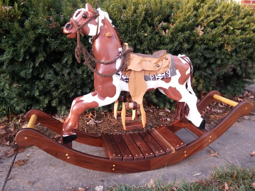 heirloom wood hand carvved rocking horse with hand made saddle and bridle, brown and white paint horse, yarn mane and tail, glass eye