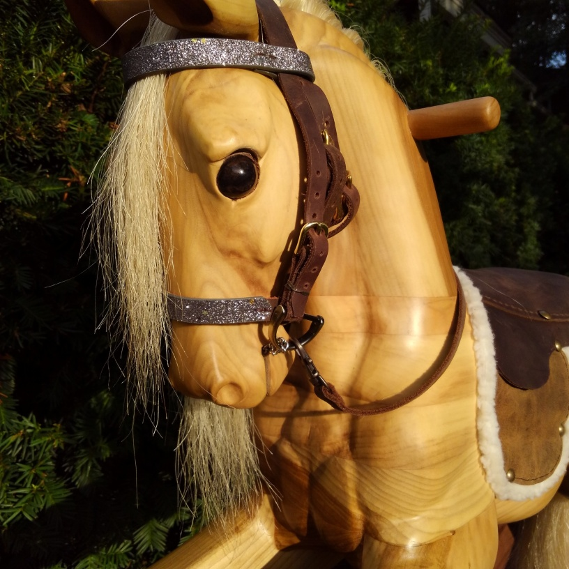 close up of wooden rocking horse, sun shining on the horse's face, showing leather bridle and sparkly noseband and browband, and horse's glass eye shining in the sun