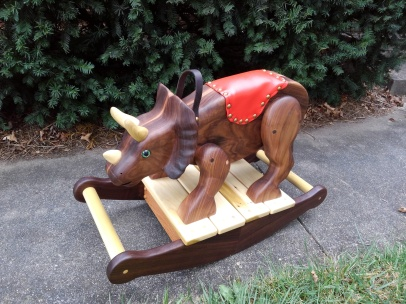 hand carved walnut triceratops rocking horse with red saddle. Sitting on sidewalk with green bushes in background. view from slightly above