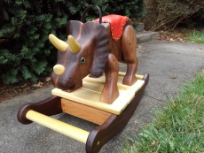 triceratops rocking horse on sidewalk with green bushes and grass in the background