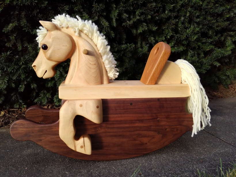 rocking horse for a toddler with maple head and legs, white wool yarn mane and tail, and walnut rockers, on a concrete sidewalk with green bushes in the background.