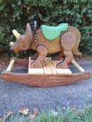 Hand carved walnut triceratops rocking horse with maple and walnut rockers,