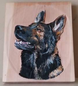 relief carving of german shepherd dog on cherry wood in acrylic paints
