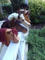10 hobby horses lined up in a row hand made from natural wood