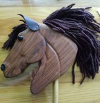 hand made walnut wood hobby horse with hand carved features, plastic eye, and brown mane, leather ears