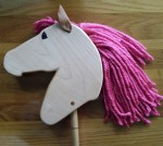 hand made maple hobby horse with hand painted eye, leather ears, and pink mane