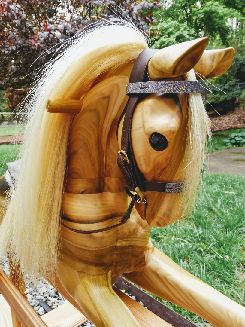 wooden rocking horse showing close up of head and neck, showing handle and leather bridle