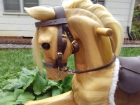 wooden rocking horse showing the head and neck with fully functioning leather bridle with buckles and bit.