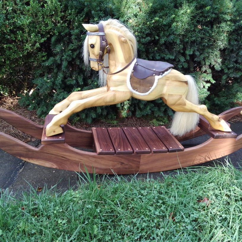 wooden rocking horse showing full view of the left side and wooden rockers