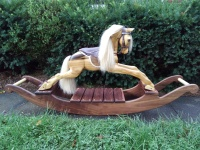 hand carved wooden rocking horse, showing the right side and full view of walnut rockers