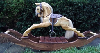 Left side of a wooden hand carved rocking horse in front of green shrubs, horse has leather saddle and bridle and real stirrups.
