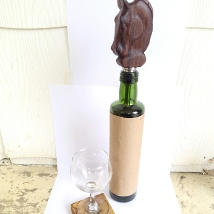 hand carved horse head in walnut wood on stainless steal wine bottle stopper, sitting on green glass olive oil bottle with brown paper wrapper.To the bottom left is a small wine glass sitting on a rustic square wood coaster