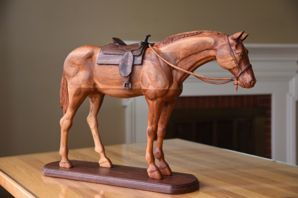 hand carved cherry wood horse standing with carved walnut saddle on walnut base. With carved bridle and rein over neck