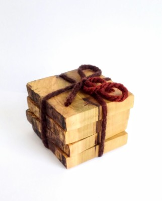 square wood coasters in poplar wood in a stack with a variegated brown yarn string holding them together with a bow.