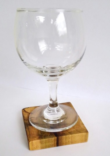 rustic wood coaster under a clear glass wine glass