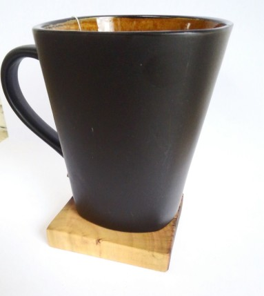 dark brown coffee mug sitting on wooden coaster with white background