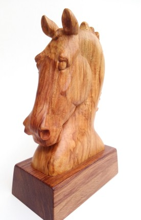 horse head carving on small stand, facing forward at an angle so you see the left side of the horse's face and the front.