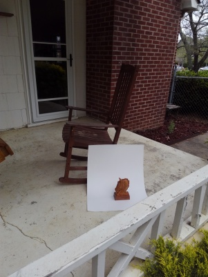 example of how to photograph small wood carving with a piece of white poster board taped to a rocking chair on an outdoor porch. Hand carved horse head sculpture is the subject being photographed