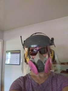 woman wearing dust respirator, ear protection, face shield, and sunglasses to protect face during power wood carving