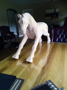 wood rocking horse placed on table, unfinished sanded beech wood