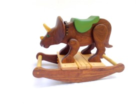 hand carved wooden triceratops dinosaur rocking toy. The dino is carved from walnut wood, left natural with oil finish. Poplar hand carved horns. It has a green painted wood saddle and leather handle. Green reptile eyes. Walnut rockers with maple slats. Small, size for 1-2 years old.