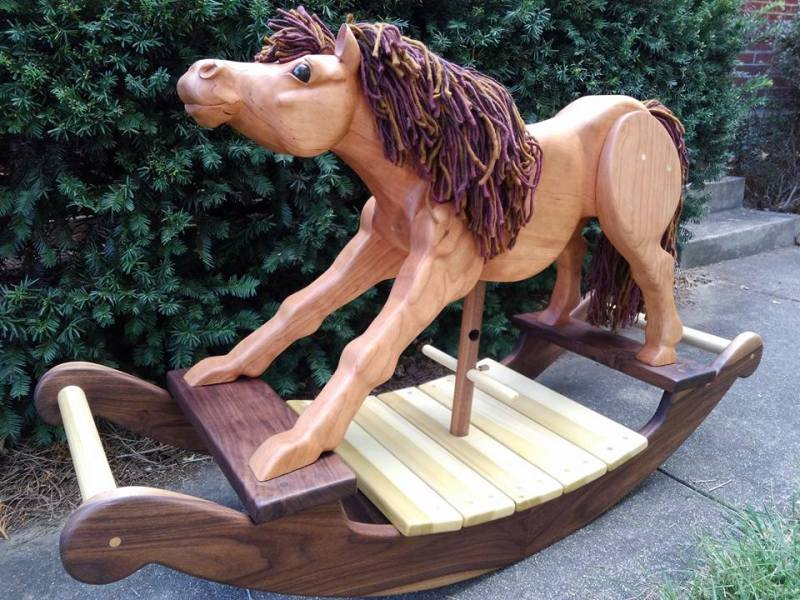 Hand carved rocking horse in cherry wood with walnut and poplar rockers. Photo of horse on sidewalk with background of green leaves. Multi-colored brown yarn mane and tail.