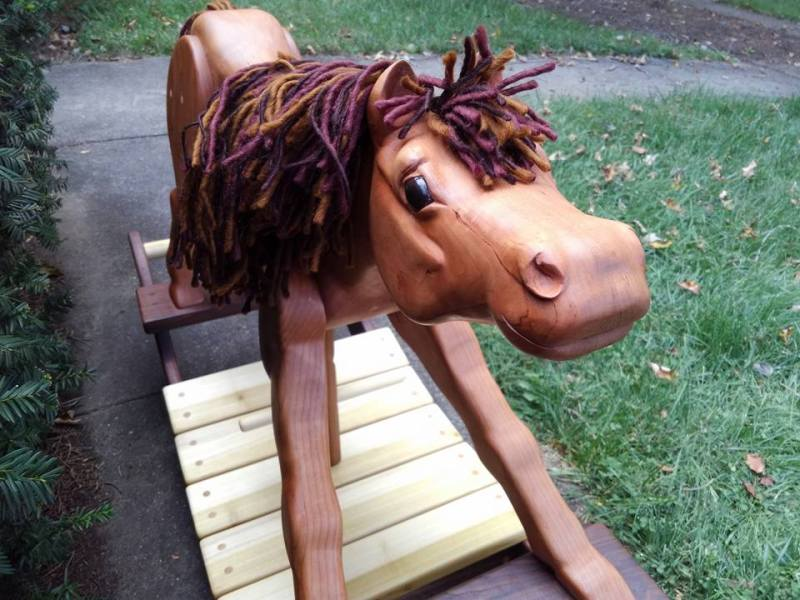 Hand carved wooden rocking horse in cherry wood with walnut and poplar rockers. hand painted eyes create a cute happy expression. horse pictured on sidewalk with background of grass and green leaves.