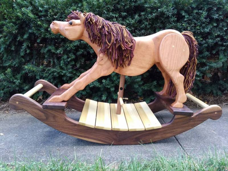 Hand carved rocking horse in cherry wood with walnut and poplar rockers. Horse stretching out front legs like it is sniffing for some apples. Multicolored brown yarn mane and tail. Pictured on sidewalk with green leaves in background.